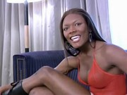 Blazing ebony shemale poses on sofa